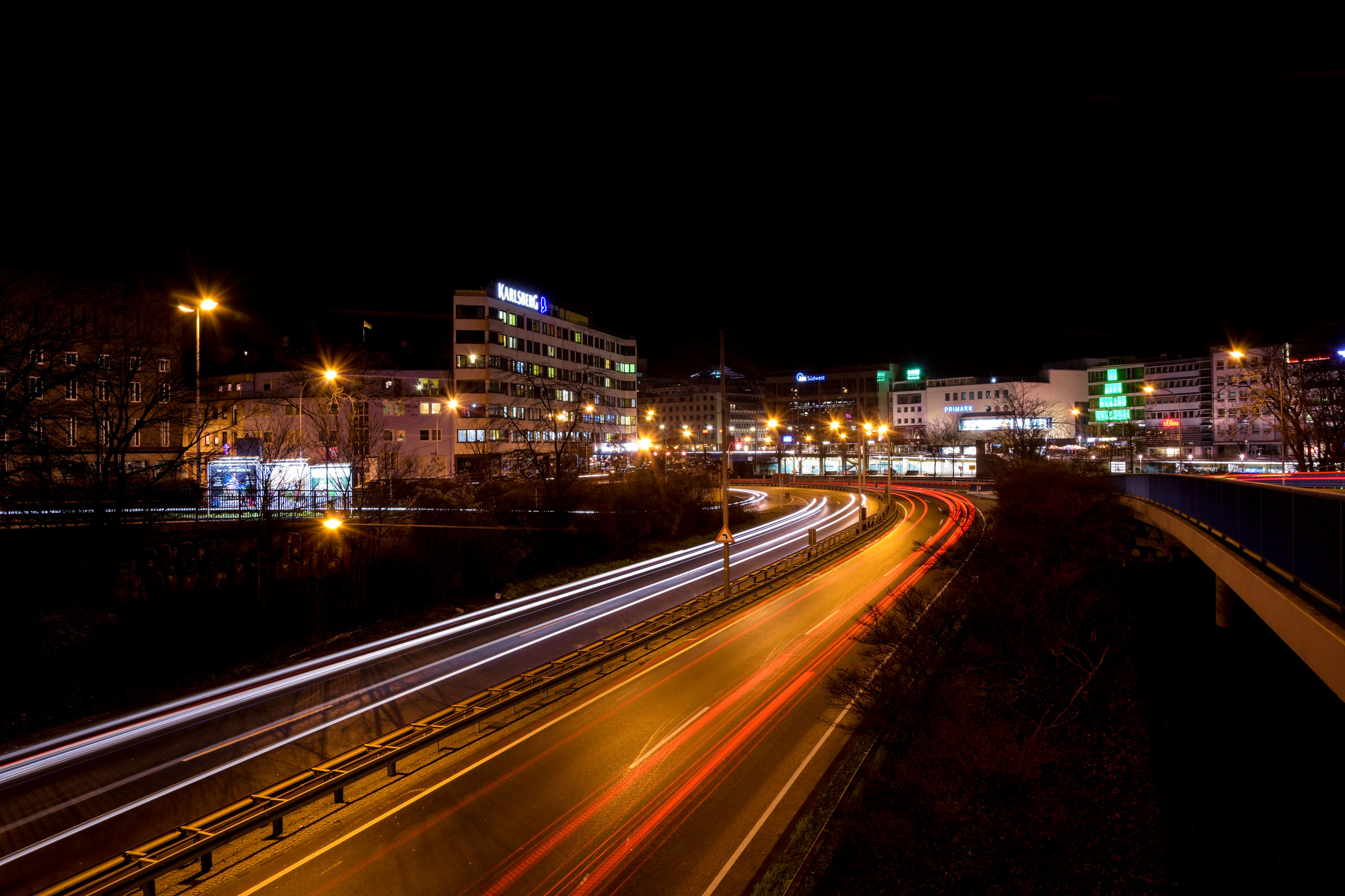 night, transportation, illuminated, city, traffic, long exposure, light trail, city life, road, high angle view, speed, motion, no people, outdoors, rush hour, business finance and industry, architecture, cityscape, sky