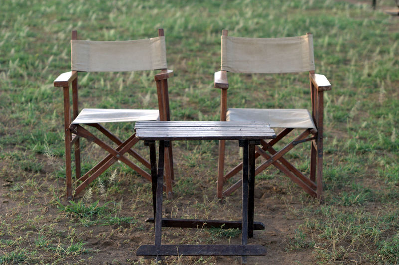 Empty foldable chairs and table on field