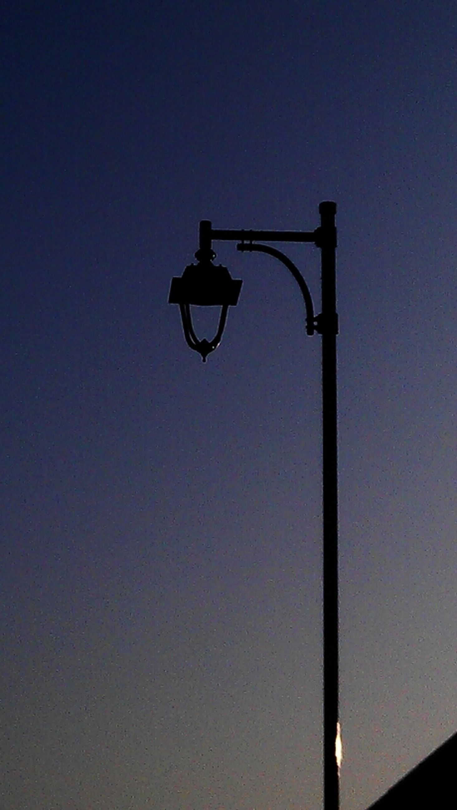 low angle view, street light, clear sky, lighting equipment, copy space, silhouette, pole, lamp post, built structure, blue, electric light, sky, architecture, no people, outdoors, cross, dusk, electricity, high section, lantern