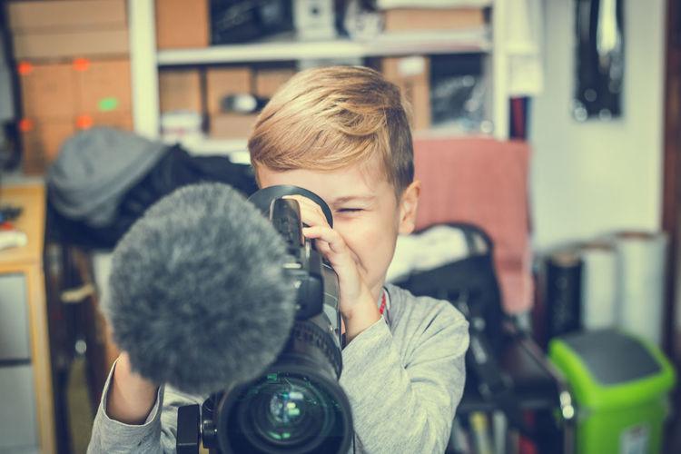 Boy using video camera at home