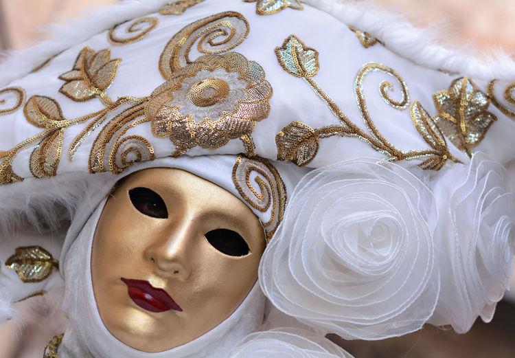 Portrait of woman wearing mask and headdress