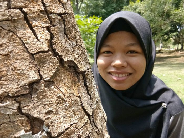 Portrait of smiling girl standing against tree trunk