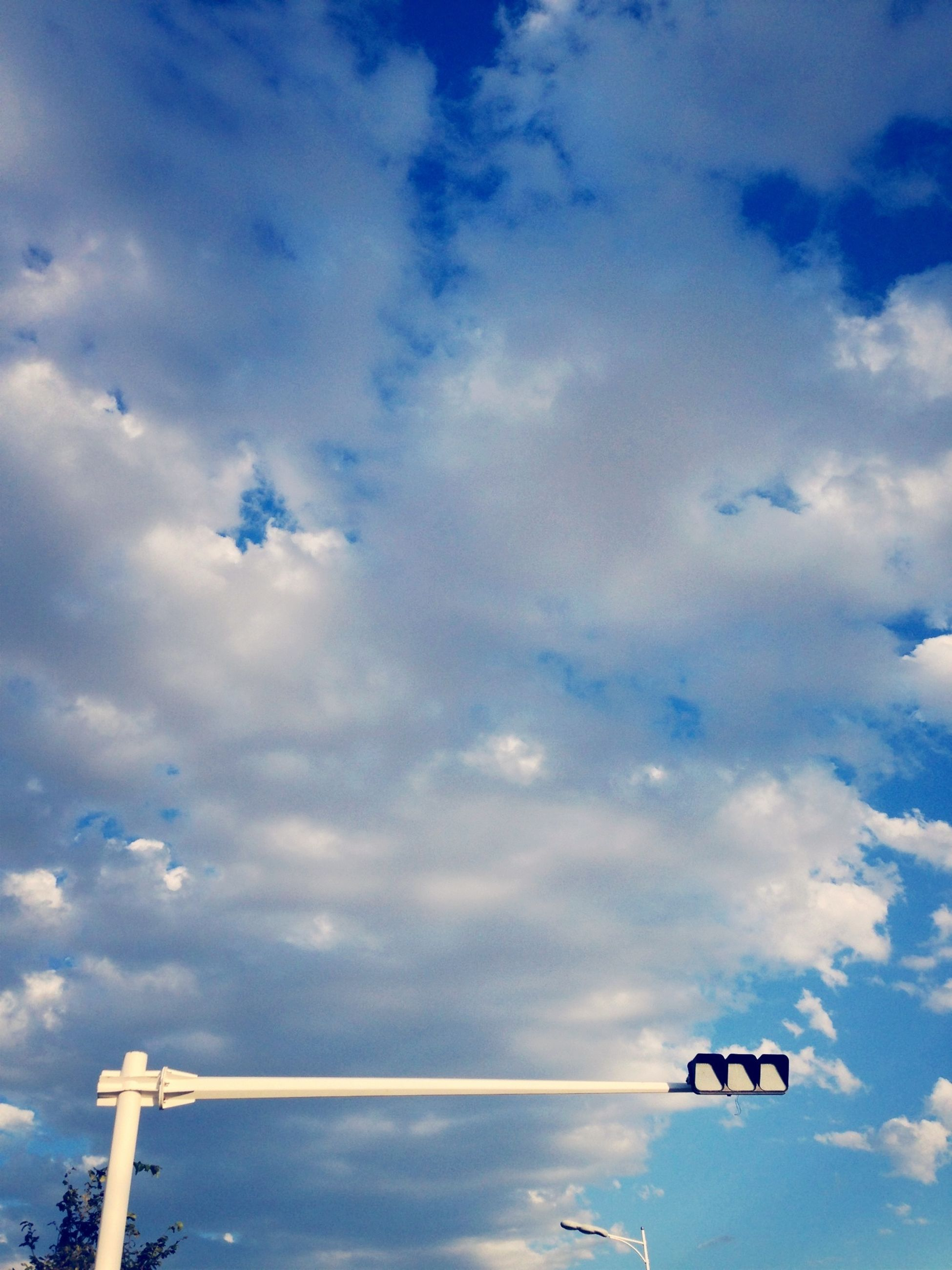 low angle view, sky, cloud - sky, blue, cloudy, cloud, transportation, street light, technology, day, outdoors, no people, nature, mode of transport, lighting equipment, communication, airplane, high section, cloudscape, electricity