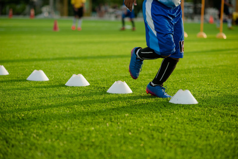 Low section of boy practicing slalom training drill on soccer field