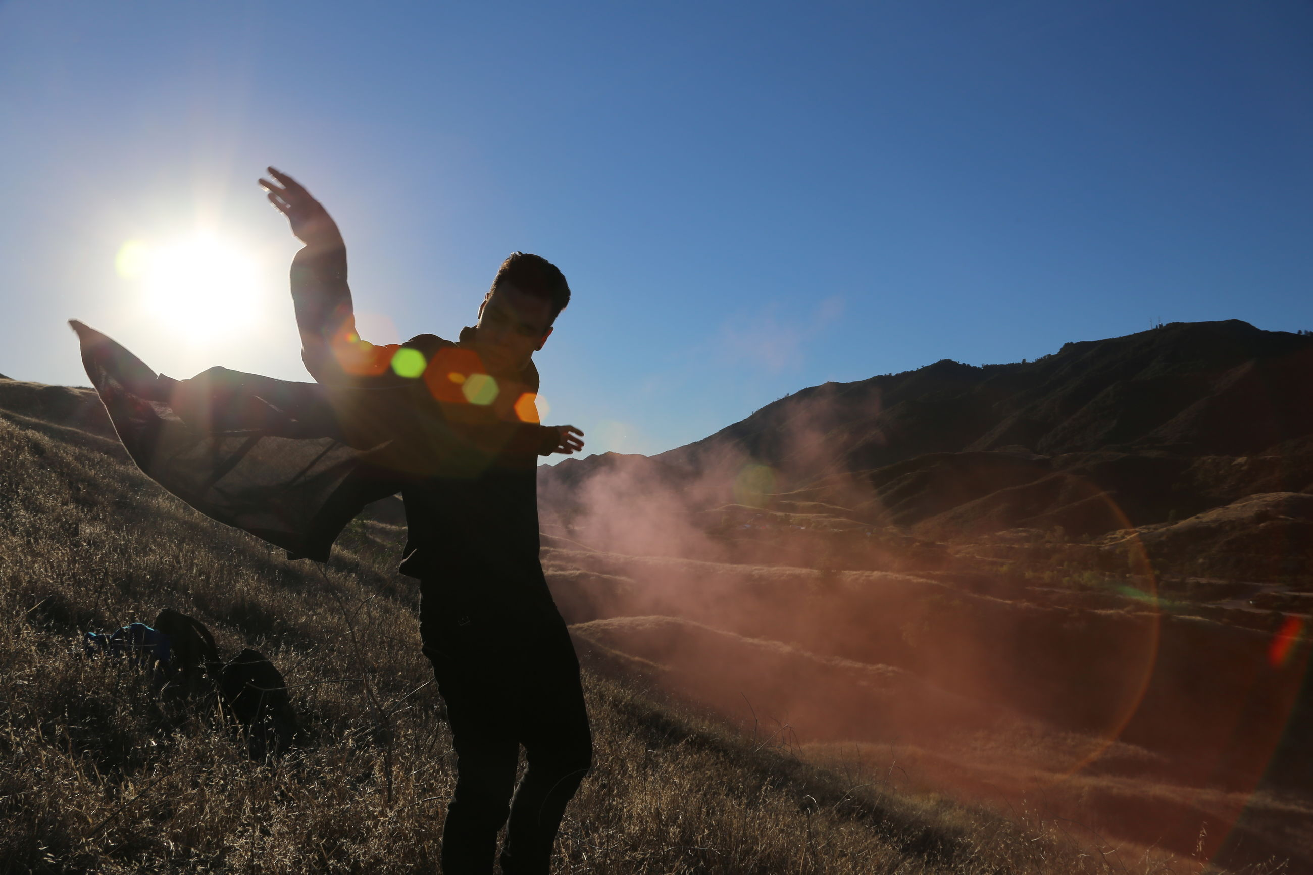 clear sky, silhouette, sun, sky, sunlight, blue, standing, lifestyles, mountain, copy space, lens flare, leisure activity, men, sunset, sunbeam, full length, nature, outdoors