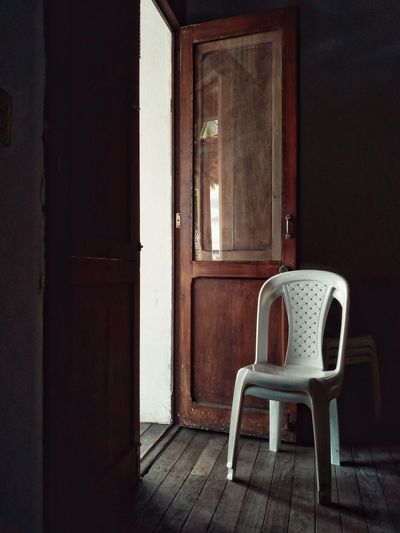 Empty chair on table by window in old house