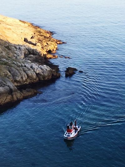 High angle view of man standing in boat on sea