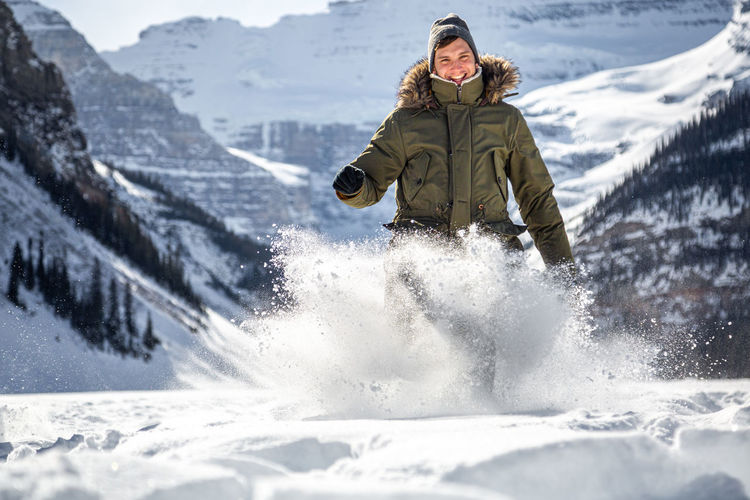 Portrait of man playing with snow on land against mountain