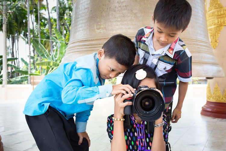 A group of local Myanmar's children are learning how to play and use DSLR camera. ASIA Fun Kids Learning Adorable Boys Camera - Photographic Equipment Child Childhood Cute Day Education Elementary Age Learning Outdoors Playing Camera Pressing Shutter Standing Togetherness Two People Welcome