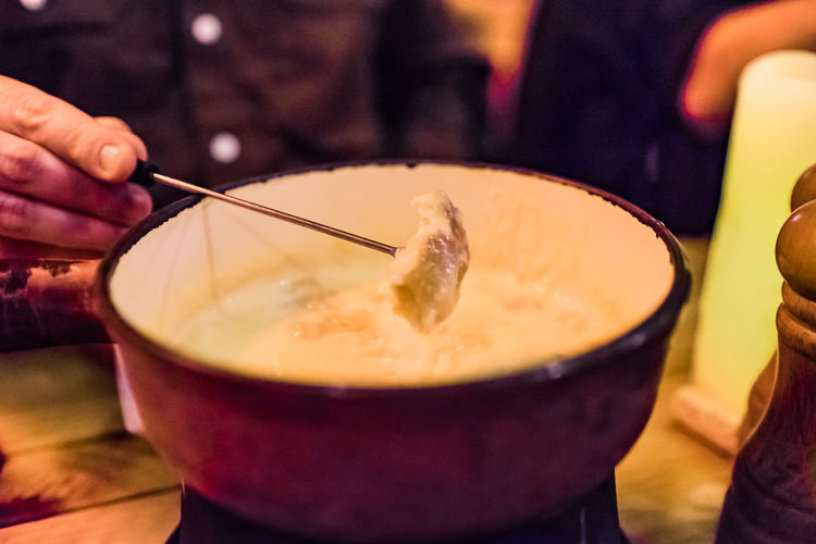 Close-up of manholding skewer on cheese fondue