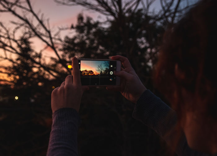 Wireless Technology Technology Photography Themes Smart Phone Portable Information Device Holding Communication Human Hand Mobile Phone Photographing Hand Activity Tree Screen One Person Connection Focus On Foreground Human Body Part Nature Plant Nature Photography Sunset Smartphone Photography Girl