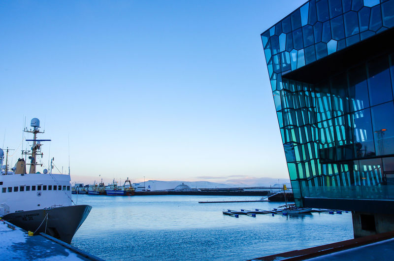 Harpa Concert Hall at Harbour of Reykjavik Harpa Iceland Reykjavik Architecture Blue Building Exterior City Clear Sky Harbor Harpa Concert Hall Mode Of Transportation Nautical Vessel No People Outdoors Sea Ship Sky Travel Travel Destinations Water