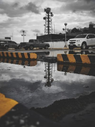 Reflection of sky in puddle on road