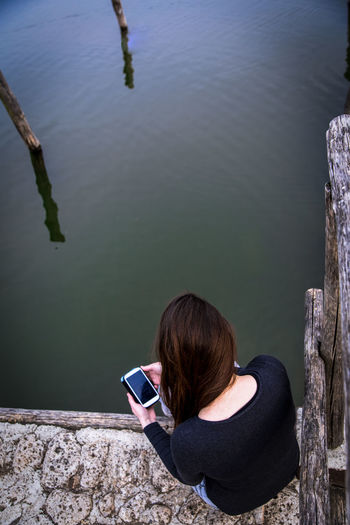 young brunette watching down on her smartphone while sitting on a pier at the lake Adult Adults Only Day High Angle View Lake Lakeshore Leisure Activity Nature One Person One Woman Only One Young Woman Only Only Women Outdoors People Relaxation Sitting Smarthphone Technology Vacations Water Women Young Adult Young Women