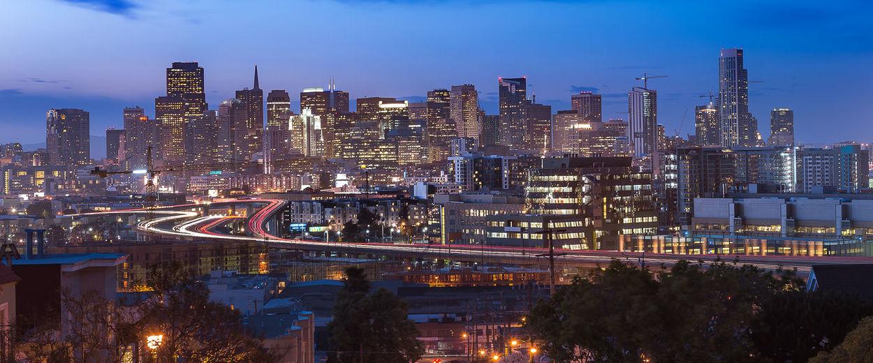 Illuminated city by buildings against sky at dusk
