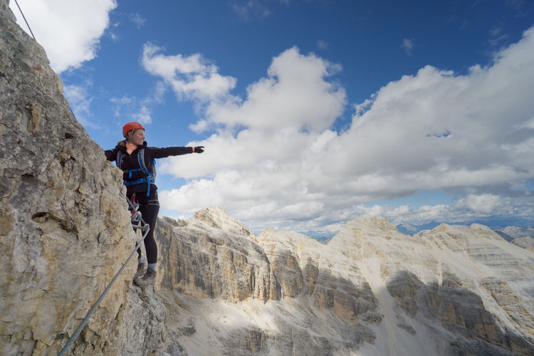 Full length of man standing on rocks against mountains and sky