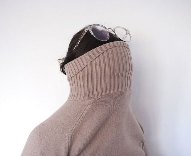 Woman With Face Covered By Turtleneck T-Shirt Against White Background