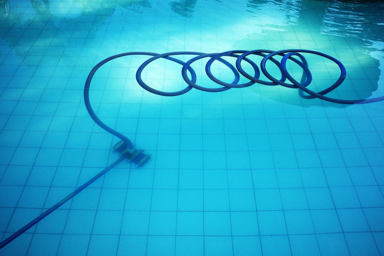 High angle view of cleaning equipment with pipe floating in swimming pool