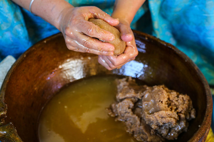 Close-up of moroccan amazigh woman hands squeezing argan paste