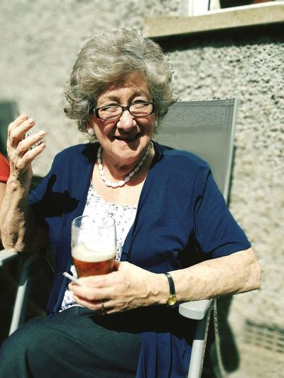 Portrait Of Smiling Woman Holding Drink While Sitting On Chair During Sunny Day