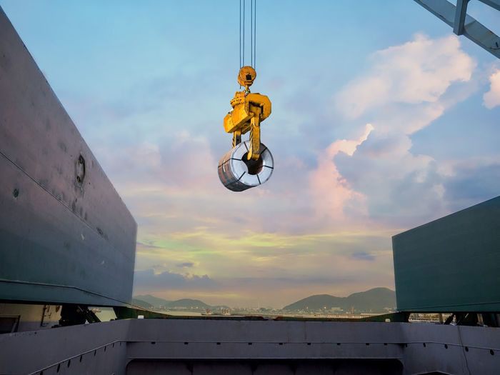 Discharging steel coil from vessel's hold to terminal warehouse Hatch Plant Stowage Adventure Architecture Berth Coil Crane Discharge Export Hold Import Loading Low Angle View Nature Outdoors Portrait RISK Skill  Sky Steel Terminal Tong Vessel Warehouse