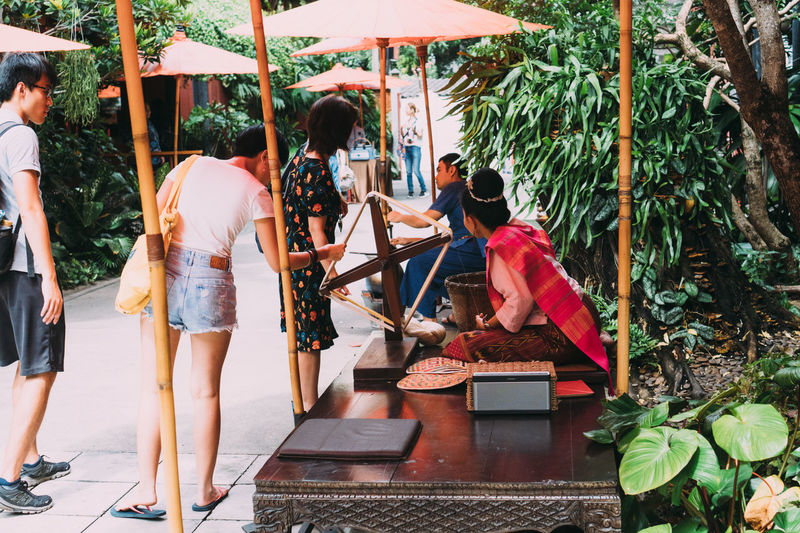 Rear view of people walking by plants