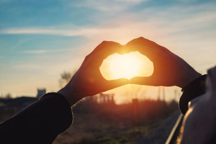 Man holding heart shape against sky during sunset