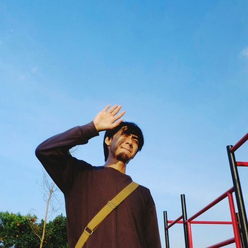 Low angle view of young man gesturing while standing against blue sky