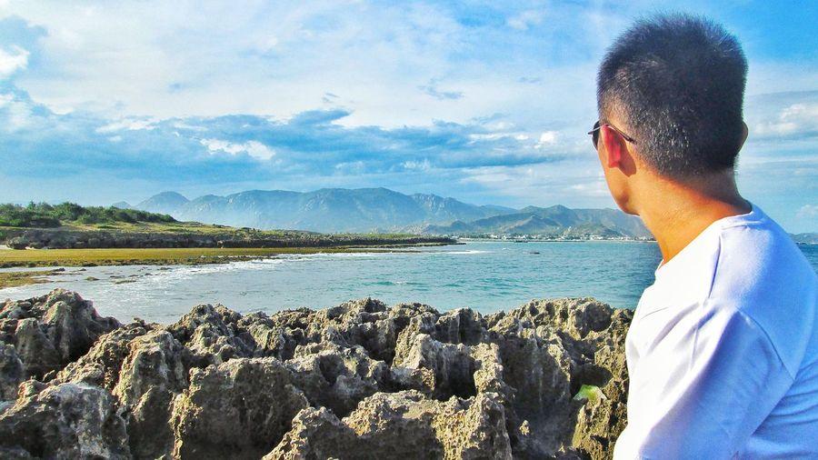 Portrait of man wearing sunglasses standing on rock against sky