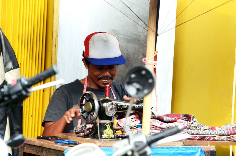 Mid adult man stitching fabrics while sitting in workshop