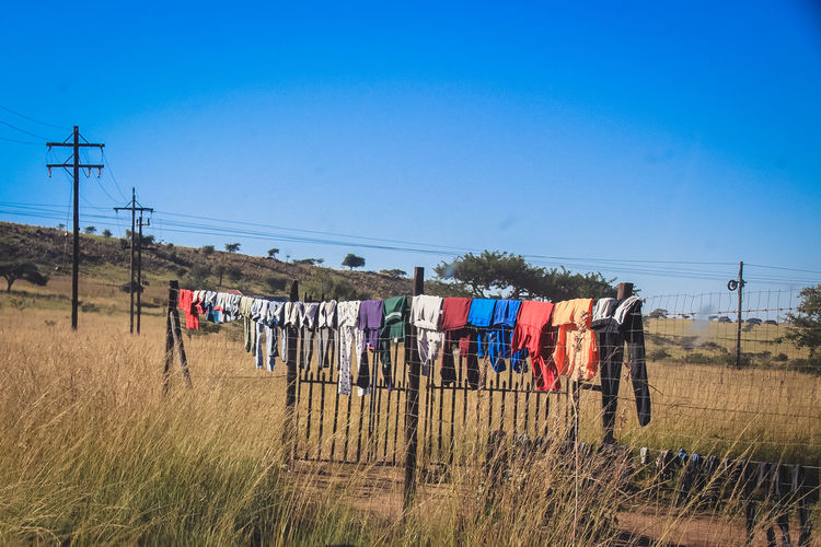 Clothes drying on field against clear blue sky