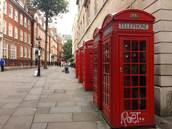 Postcode Postcards London! Red Telephone Booth Architecture Building Exterior Street Built Structure Communication City Outdoors Pay Phone Text City Street Day Telephone Travel Destinations Road No People Police Station Sky The Street Photographer - 2018 EyeEm Awards