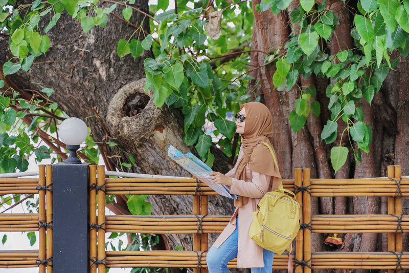 Woman sitting on wood by tree
