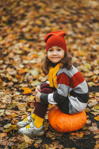 Happy cute little girl child in warm clothes sitting on a pumpkin in the autumn forest outdoors