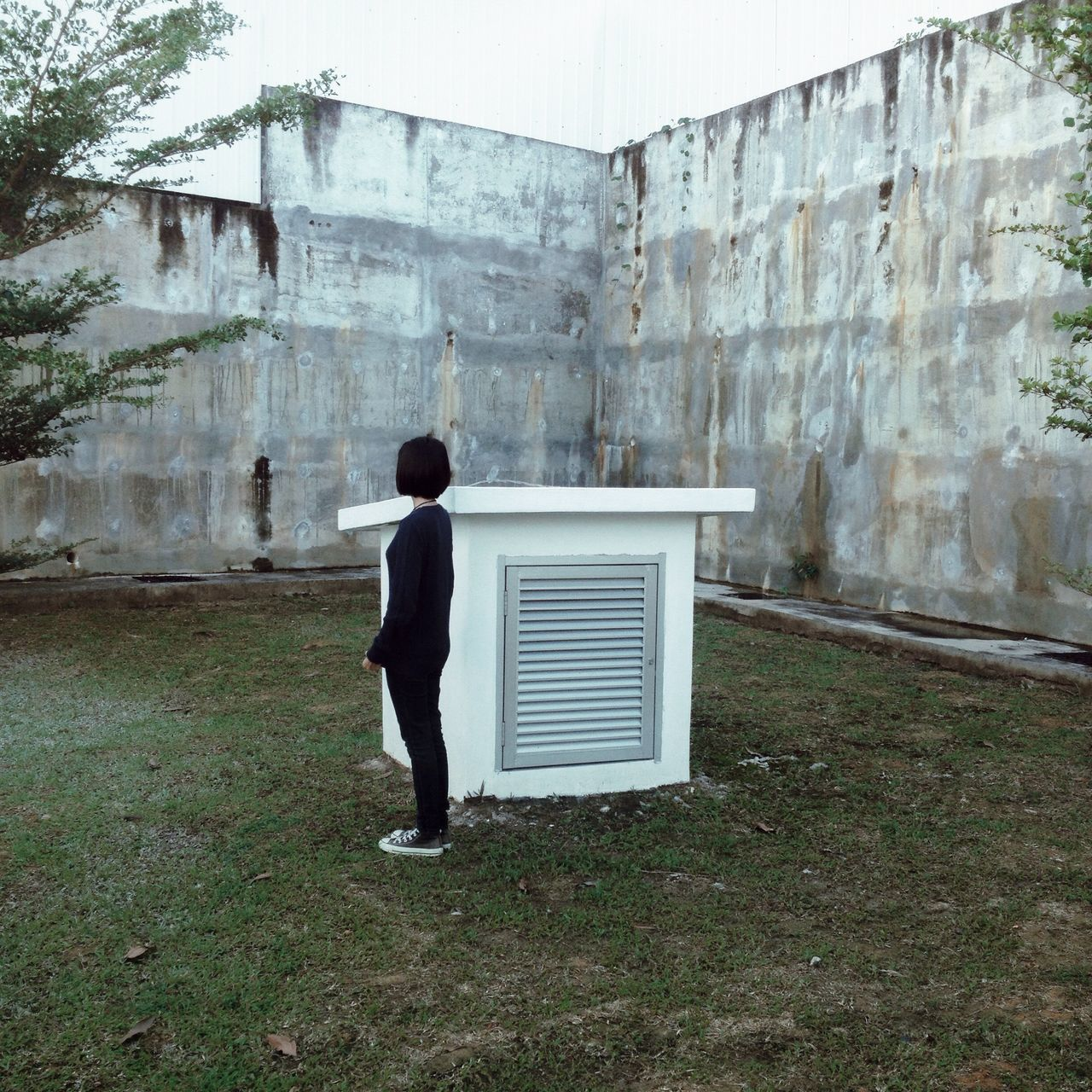 Full length side view of woman standing on field by vent