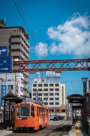 Train on railroad tracks by buildings against sky