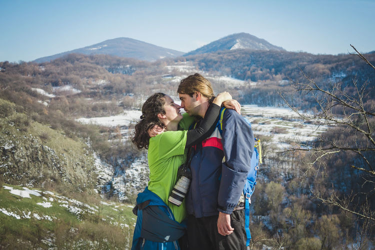Couple kissing while standing on mountain against sky