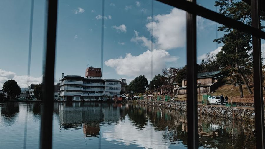 Panoramic view of lake by buildings against sky