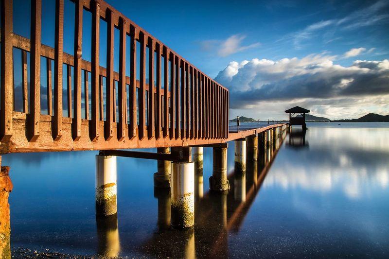 Pier over river against sky