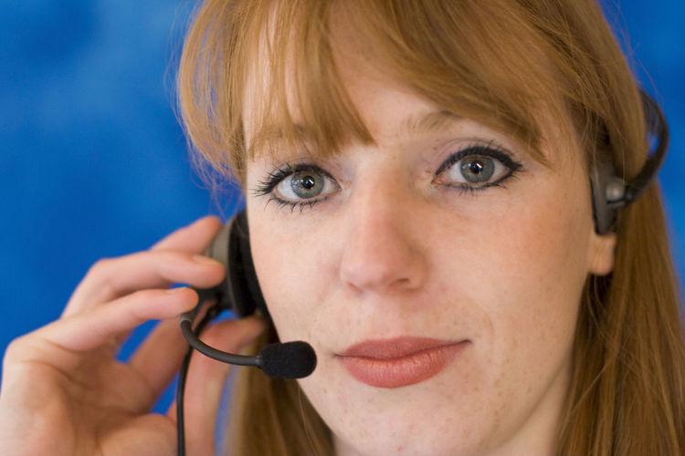 Close-up portrait of female customer service representative by blue wall