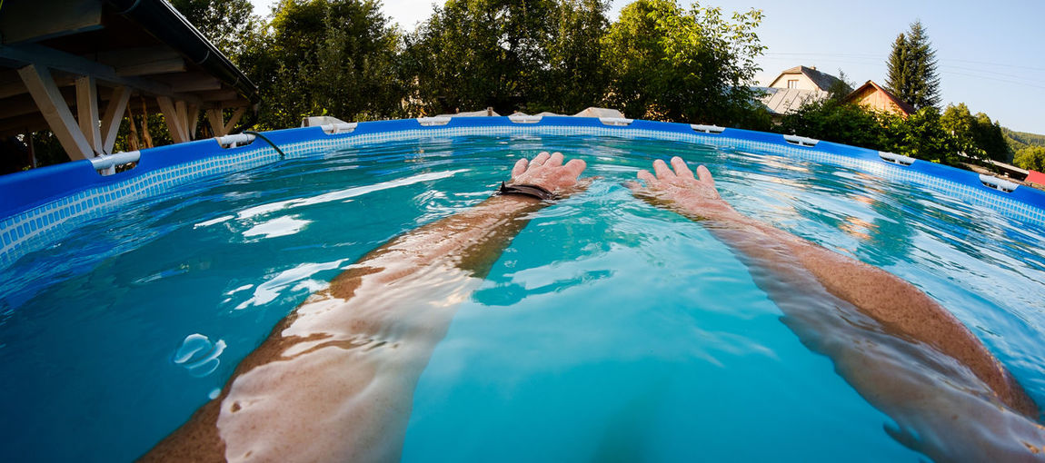 Cropped Hands Of Man In Wading Pool At Yard