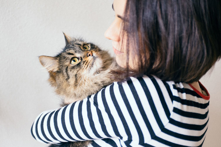 Close-up of woman holding cat against white background