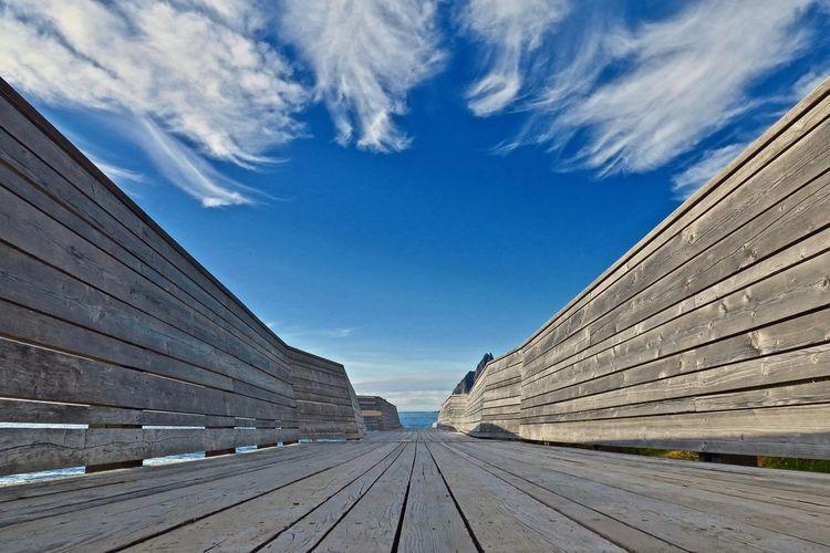 Wooden footbridge against blue sky