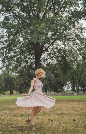 Curly Hair Girl Tree Plant One Person Full Length Women Nature Blond Hair Dancing Day Young Adult Happiness Smiling Standing Hair Lifestyles Grass Adult Land Fashion Outdoors Beautiful Woman Hairstyle