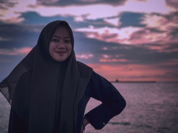 Portrait of smiling woman standing against sea during sunset