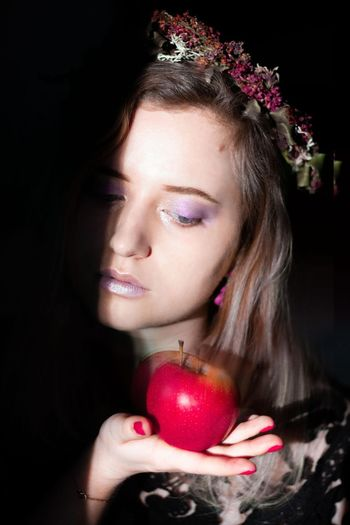 Close-up portrait of a woman holding apple