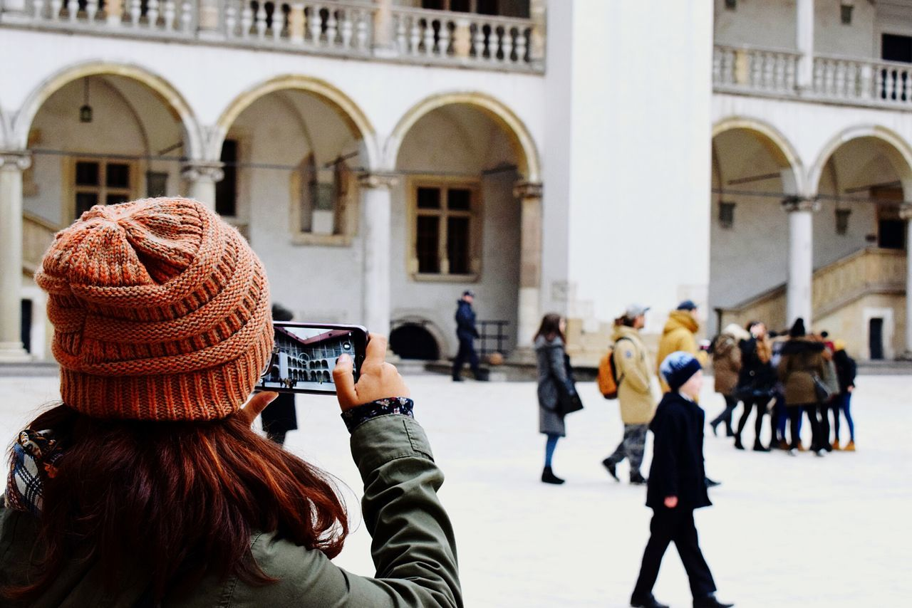 real people, rear view, architecture, photographing, women, focus on foreground, building exterior, leisure activity, built structure, photography themes, lifestyles, one person, city, camera - photographic equipment, outdoors, day, close-up, people