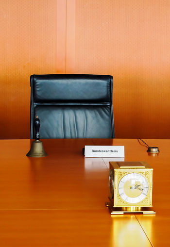 Clock And Bell With Nameplate On Table At Office