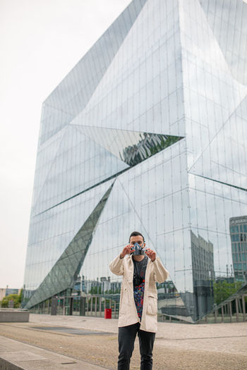 Full length of woman standing against modern office building