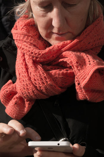 Woman Wearing Warm Clothing Using Mobile Phone Outdoors